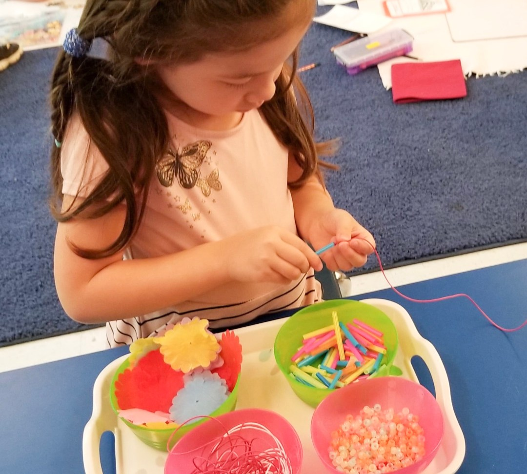 A child threading beads onto a necklace demonstrates character development in early childhood classrooms.