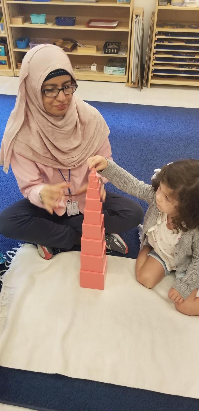 A teacher working with a student at Children's House Montessori School of Reston