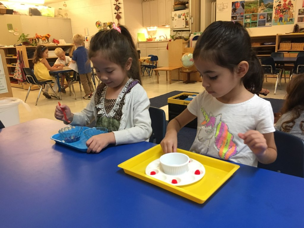 Two children using practical life materials at Children's House Montessori School of Reston
