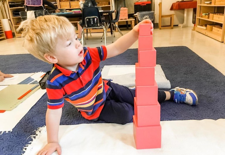 Working on the pink tower at Children's House Montessori School of Reston