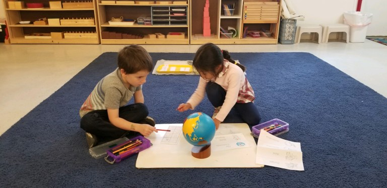 children working together with a globe / signs of readiness for preschool