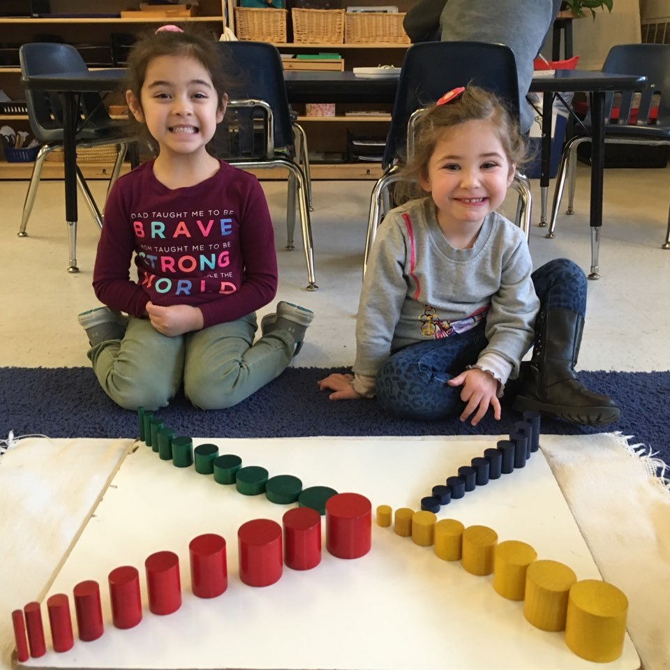Two children proudly showing their work with the Sensorial colored cylinders, part of the Montessori curriculum.