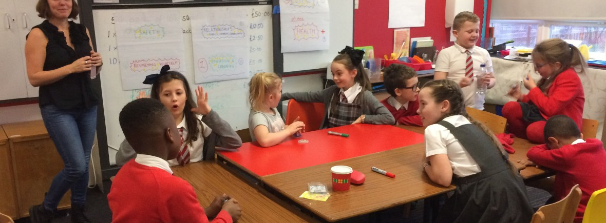 A researcher with a group of primary school children from the Bridgeton and Dalmarnock neighbourhood undertaking group work