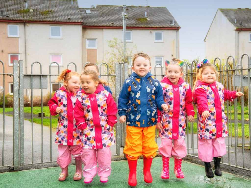 A group of children in raincoats jumping in a play park