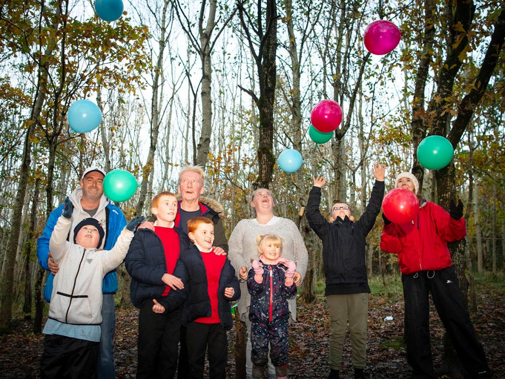 A group of children and adults throw blue, pink and green balloons into the air while standing in a woodland
