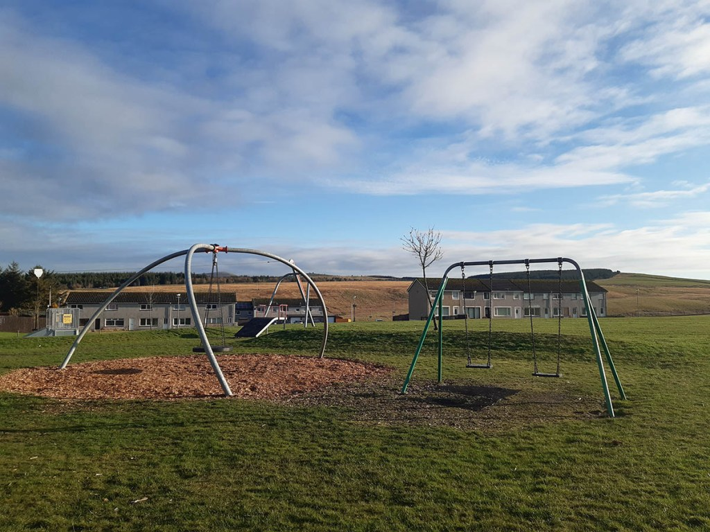 View of grassy fields with children's swings