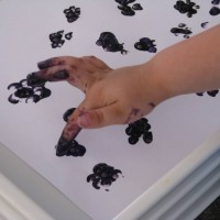 A child make blackberry finger painting