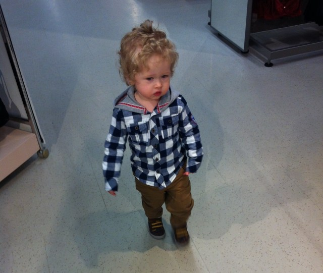 Tesco Blue and white checked shirt with hood. Tan trousers and brown boots, Lucas walking on white tiled floor