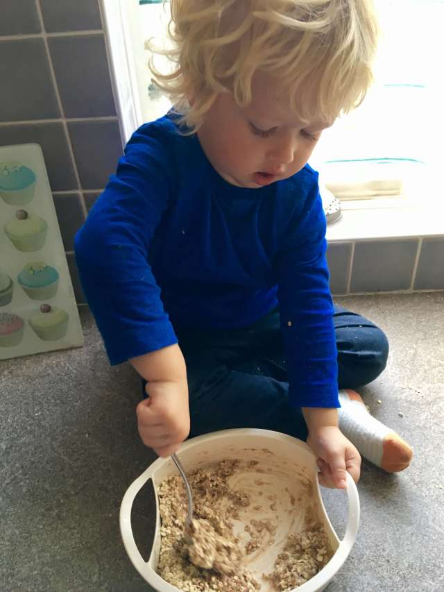 Savoury flapjack recipe Lucas is sat on a grey worktop stirring oats in a bowl
