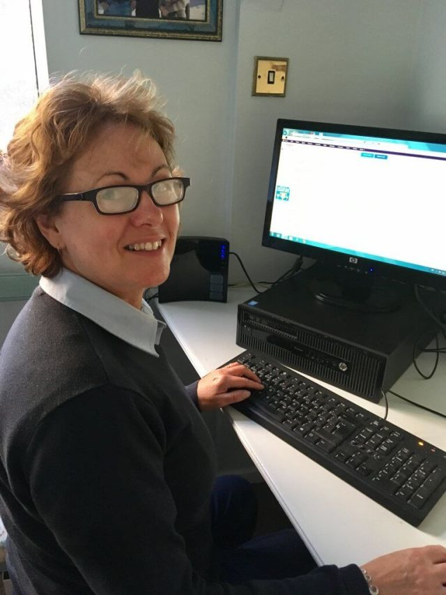Eyejusters review my mum (a woman in her 50s with dark brown short curly hair) is sat at the computer wearing a navy work uniform looking at the camera with purple glasses on