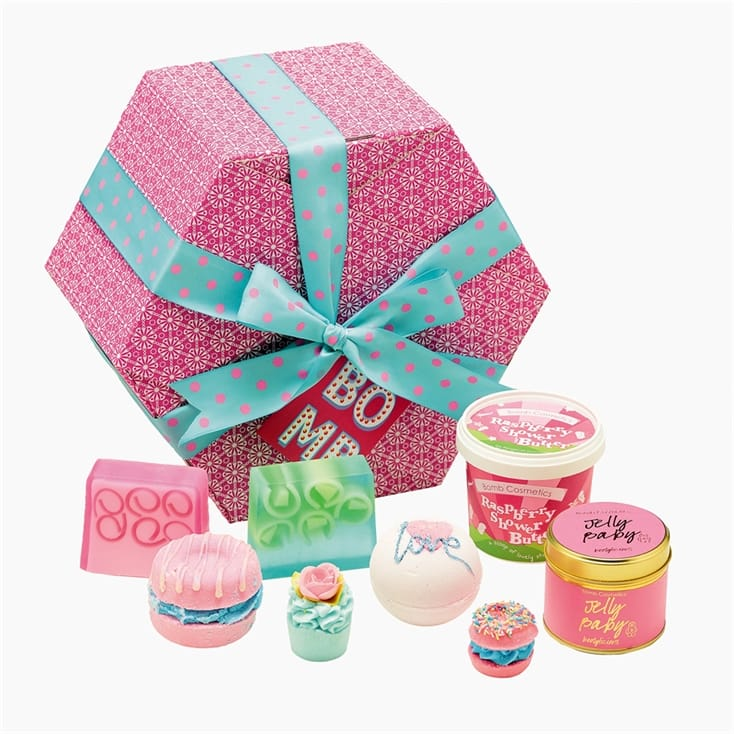 Mother's Day gift ideas a pink hexagon patterned box with blue ribbon and pink spots on, wrapped around the box in a bow. a selection of products in front of the box, soap, bath bombs and a candle