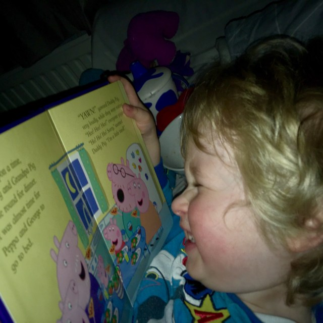 Bath, book, bed (and maybe a little creativity) Lucas has blonde wavy hair he is smiling at a book, the camera has a side on angle