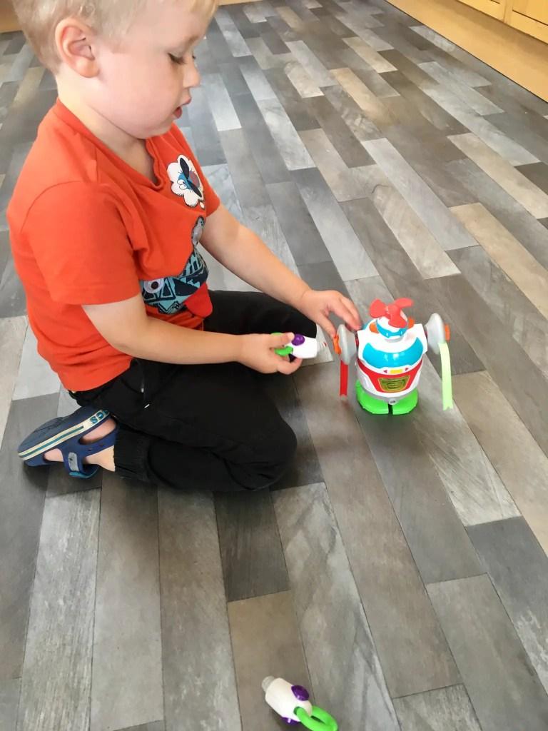 Little Tikes STEM Jr review Lucas kneeling on floor, building the robot