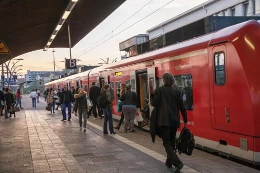 S-Bahn am Bahnsteig. Viele Menschen steigen aus und ein.