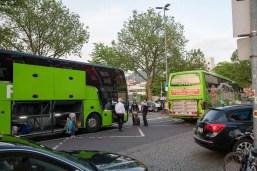 Zwei Busse. Busfahrer zeigen einer Reisenden den richtigen Bus.