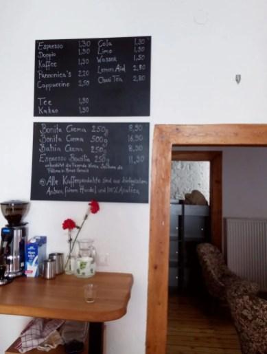 Im Vordergrund hängen Tafeln an der Wand, die die Getränkepreise zeigen. Darunter eine Kaffeemühle und Blumen