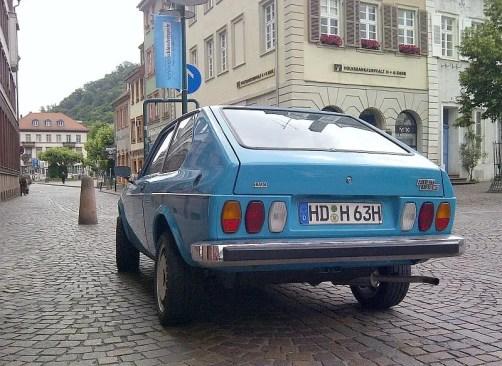 Blauer Fiat Oldtimer von hinten aufgenommen vor dem Rathaus