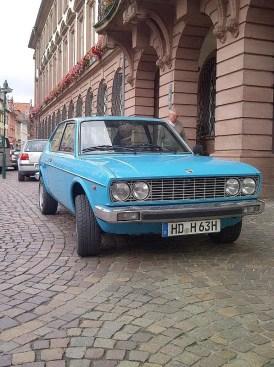 Blauer Fiat Oldtimer von vorne aufgenommen vor dem Rathaus