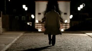 Silhouette eines Mannes über die schwach beleuchtete Brücke geht.