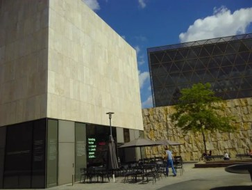DAs Museum ist ein Kubus. Außen stehen Stühle.