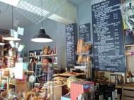 Eine Verkäuferin ist zu sehen und dahinter eine große Tafel mit dem Brot- und Frühstücksangebot.