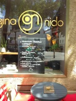 Schaufenster mit Angebot des Cafés auf einer Tafel.