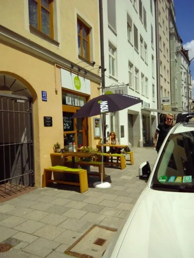 Zwei Tische und Bänke für etwa acht Personen stehen vor dem Restaurant.