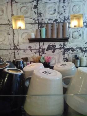 Hinter der Kaffeemaschine stehen Becher gestapelt.