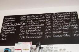 Eine schwarze Tafel. Darauf stehen in weiß die Getränke mit den Preisen