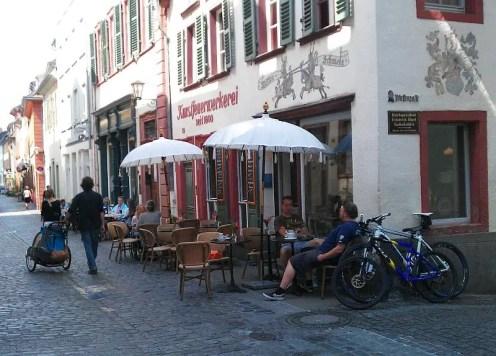 Verziertes Gebäude in der Seitenansicht. Davor Stühle, Tische und zwei Sonnenschirme. Blick in die Untere Straße.