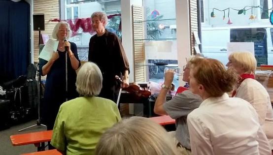 Frau Hoffmann und Herr Petermann am Mikrofon, davor Gäste