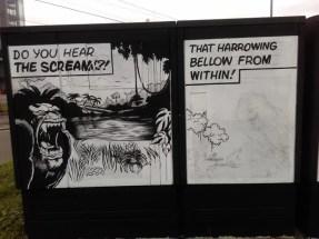 Ein schwarzer Stromkasten mit einem weißen Schild. Darauf ist mit schwarzer Farbe comicartig gemalt.