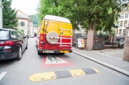Theaterstraße und ein bunter Bus. Auf dem Boden ist ein Vorsicht-Schild mit spielenden Kindern aufgemalt und eine Bodenschwelle.