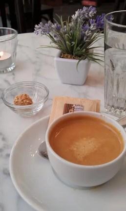 Doppelter Espresso in einer weißen Tasse, ein Gläschen Wasser und etwas zu Naschen