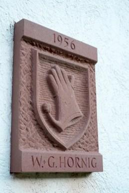 Steinplatte mit Handschuh als Wappen.