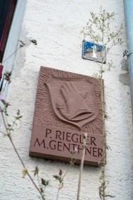 Steinplatte gemeißelt. Hausnummer 1 und Handschuh-Wappen. Schriftzug P. Riegler M. Genthner.