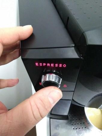 Eine Hand drückt auf den Startknopf der Maschine.