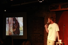 Comedian with another photo of Burrito from the slideshow on screen.