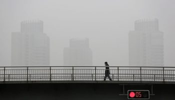 A man wearing a face mask walks on the bund near the financial district of Pudong amid heavy smog in Shanghai