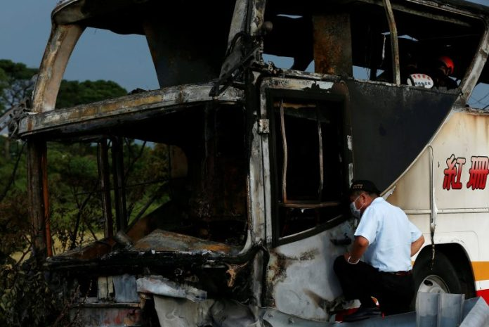 A worker looks at the wreckage of a bus carrying tourists from China which crashed into a highway railing en route to Taoyuan airport is seen, just south of the capital Taipei, Taiwan July 19, 2016. REUTERS/Tyrone Siu