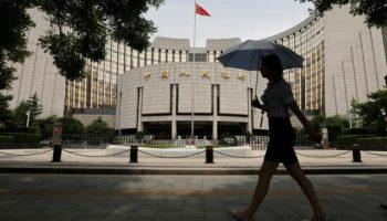Woman walks past the headquarters of the PBOC in Beijing