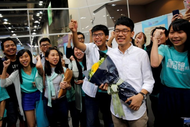 Student leader Joshua Wong (C) greets candidate Nathan Law (2nd R) as supporters share their joy after Law won in the Legislative Council election in Hong Kong, China September 5, 2016. REUTERS/Tyrone Siu