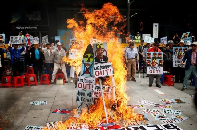 A cut-out of North Korean leader Kim Jong Un is set on fire during an anti-North Korea rally in central Seoul, South Korea, September 10, 2016. REUTERS/Kim Hong-Ji
