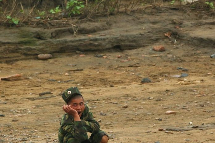 A North Korean soldier sits at the bank of the Yalu River, near the North Korean town of Sinuiju, opposite Dandong in China's Liaoning province, September 10, 2016. REUTERS/Thomas Peter