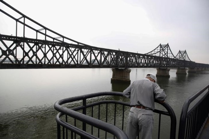 Looks at the Yalu River from the destroyed bridge that once linked North Korea's Sinuiju and Dandong in China's Liaoning province, September 10, 2016.  REUTERS/Thomas Peter