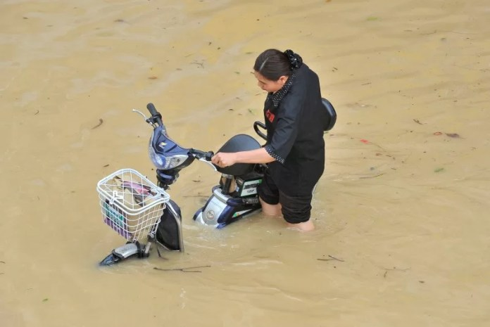A woman pushes her electric bicycle as she wades through a flooded street after Typhoon Meranti made landfall on southeastern China, in Fuzhou, Fujian province, China, September 15, 2016. REUTERS/Stringer