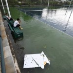 People sit on bench inside a flooded tennis court after Typhoon Meranti makes a landfall on southeastern China, in Xiamen
