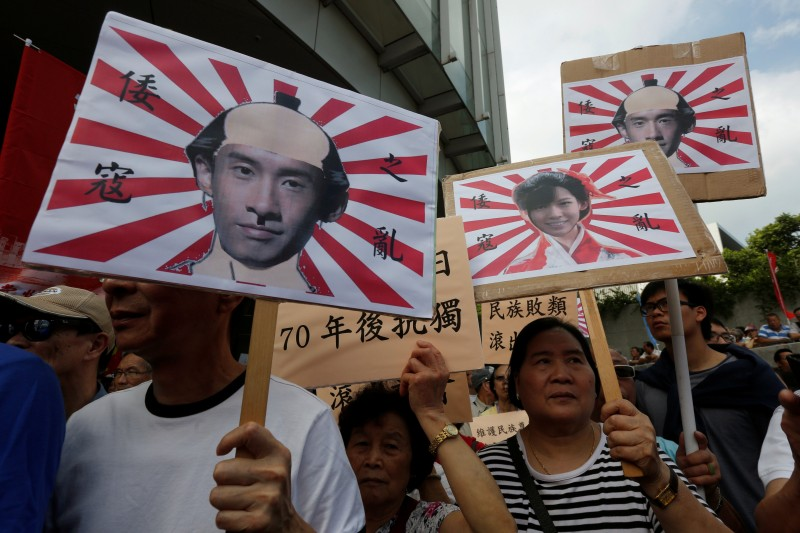 Pro-China protesters carry printouts depicting legislator-elects Baggio Leung (L, R) and Yau Wai-ching (C) as traitors during a demonstration outside the Legislative Council in Hong Kong, China October 26, 2016.  REUTERS/Bobby Yip