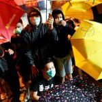 Demonstrators try to protect themselves from being pepper-sprayed during a protest in Hong Kong