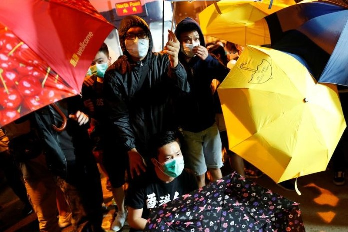 Demonstrators try to protect themselves from being pepper-sprayed during a protest against what they call Beijing's interference over local politics and the rule of law  in Hong Kong, China November 6, 2016. REUTERS/Tyrone Siu